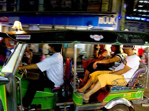 Tuk-tuk with tourists Bangkok downtown at night.