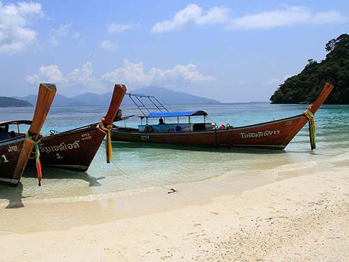 Long-tail boats stranded in a tropical beach.