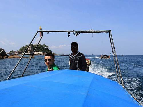 Long-tail boat sailing in the Andaman Sea.
