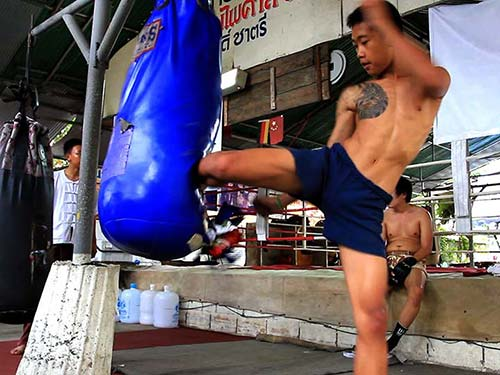 Boxer training in a gym, kicking a sack.