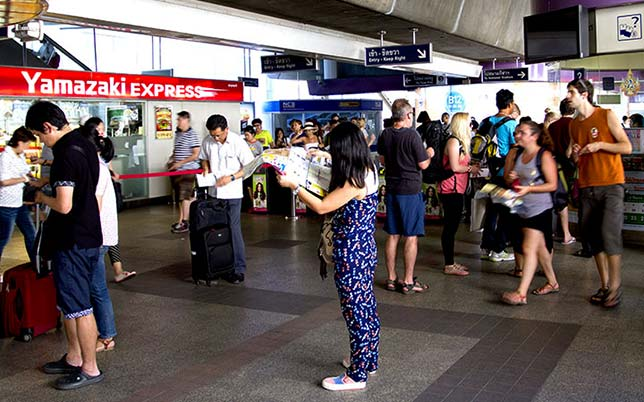 Tourist looking for information on a map, in a Bangkok Skytrain station.